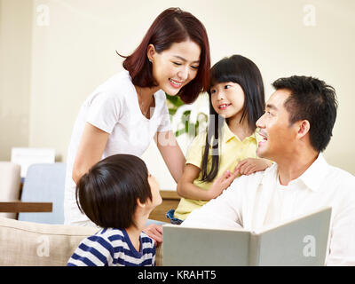asian parents mother and father and two children son and daughter reading a book telling a story together. - Stock Photo