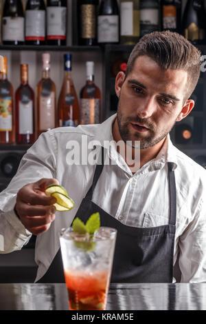 Barman decorating cocktail - Stock Photo