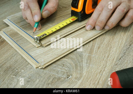 Man is preparing for installation of laminate flooring. Renovation of floor. - Stock Photo