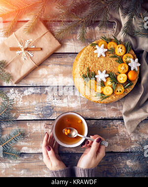 Christmas Honey cake on the table. Woman holding tea with berry near decorated present at breakfast. - Stock Photo