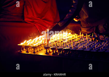 Monk fire the oil lamps of peace in the Buddhist Temple in Kathmandu