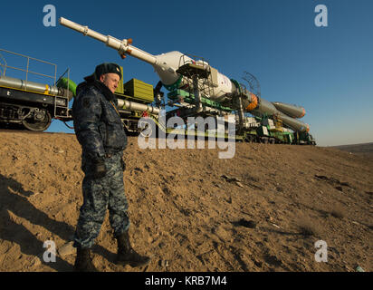 A Russian security guard is seen as the Soyuz rocket is rolled out to the launch pad by train on Tuesday, March - Stock Photo