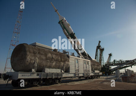 The Soyuz rocket is erected into position after being rolled out to the launch pad by train on Tuesday, March 26, - Stock Photo