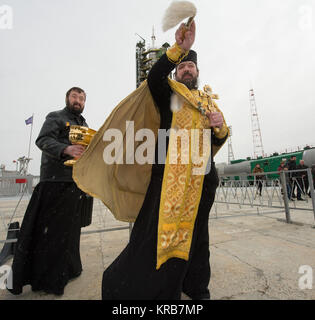An Orthodox priest blesses members of the media shortly after blessing the Soyuz rocket at the Baikonur Cosmodrome - Stock Photo