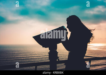 Silhouette of a young woman looking through coin operated binoculars - Stock Photo