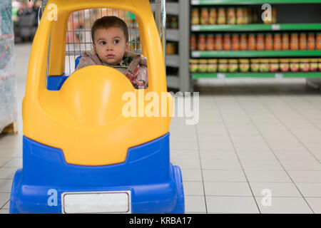 Toddler boy in a cart in the supermarket - Stock Photo
