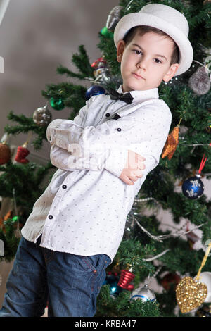 boy with serious attitude with cross arms in a blue jeans and white shirt with black bow tie and festive white hat - Stock Photo