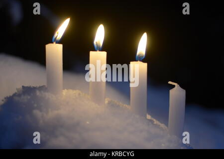 Three burning candles of white candles outdoor in the snow - Stock Photo