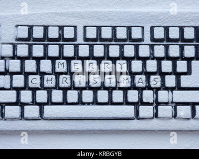 computer keyboard covered with white snow with inscription merry christmas - Stock Photo