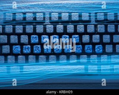 keyboard with text merry christmas on buttons covered with snow illuminated by blue neon light with light traces - Stock Photo