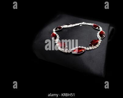 Jewellery silver ruby diamonds bracelet isolated on black cloth background - Stock Photo