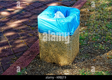 small stones trash can with a blue garbage bag the stones are probably held together by cement you can see a white - Stock Photo