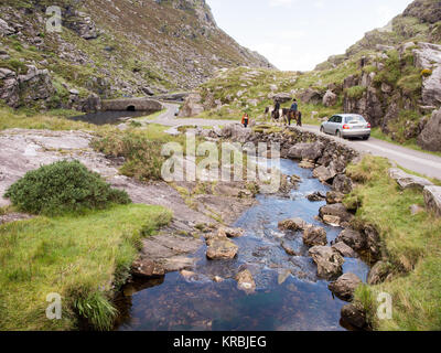 The River Loe and narrow mountain pass road wind through the steep valley of the Gap of Dunloe, nestled in the Macgillycuddy's - Stock Photo