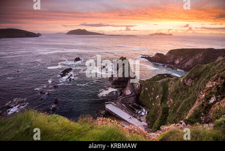 Sunset over Dunquin Pier and the Blasket Islands on the rocky Atlantic coast of Dingle Peninsula in Ireland's County - Stock Photo