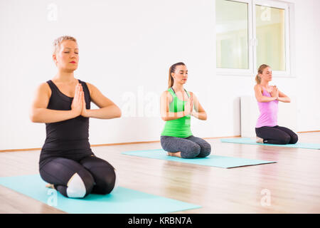 Three girls practicing yoga, Padmasana / Lotus Position - Stock Photo
