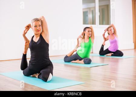 Three girls practicing yoga, Eka pada Rajakapotasana / Pigeon pose - Stock Photo