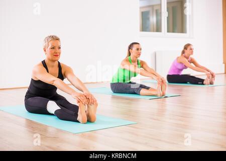 Three girls practicing yoga, Paschimottanasana / Seated Forward Bend pose - Stock Photo