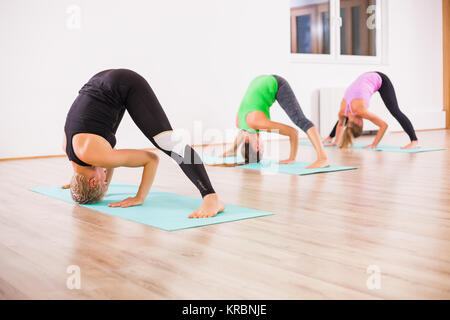 Three girls practicing yoga, - Stock Photo
