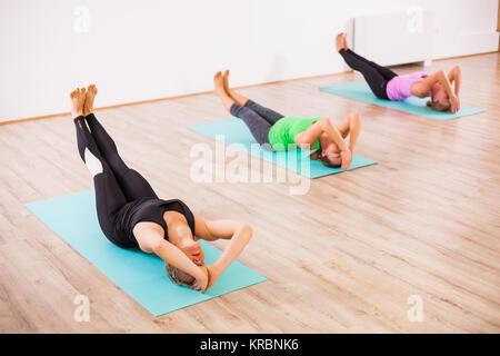 Three girls practicing yoga, Matsyasana / Fish pose - Stock Photo