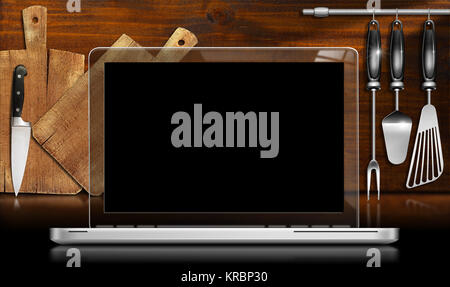 Laptop computer with black and transparent screen in a kitchen with cutting boards and utensils on wooden wall. - Stock Photo