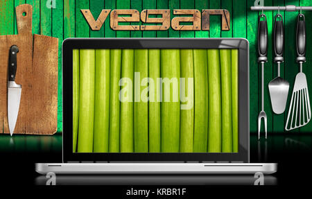 Laptop computer with green vegetables in the screen in a kitchen with cutting board and utensils on wooden green - Stock Photo