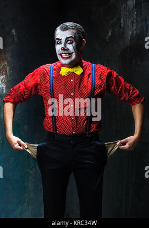 Terrible clown and Halloween theme: Crazy red clown in a shirt with suspenders on a dark background - Stock Photo