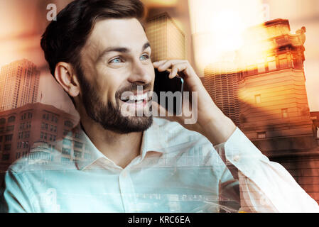 Surprised young man listening to good news on the phone - Stock Photo