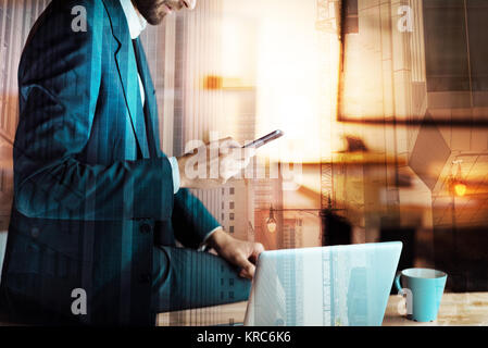 Classy-dressed businessman sitting on table and texting his partner - Stock Photo