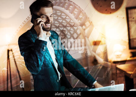 Upbeat businessman talking on the phone and smiling - Stock Photo