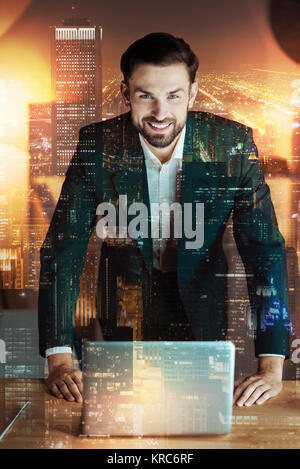 Pleasant businessman leaning on table with laptop - Stock Photo