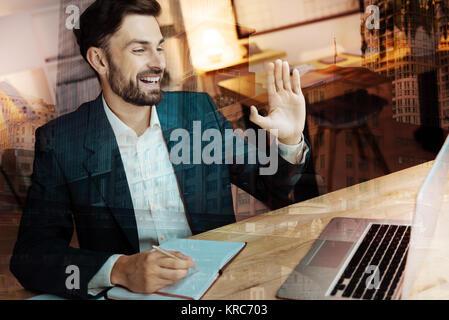 Cheerful businessman greeting his interlocutor through web camera - Stock Photo