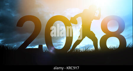 American football player running  against blue sky over grass - Stock Photo