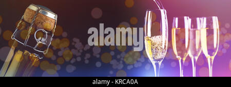 Full glasses of champagne and one being filled against sealed champagne bottle - Stock Photo