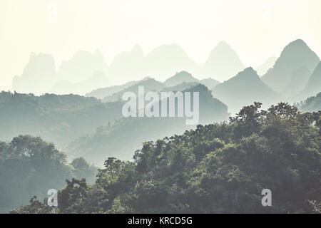 Retro toned Karst mountainous landscape around Guilin on a foggy day. It is one of China top tourist destinations. - Stock Photo