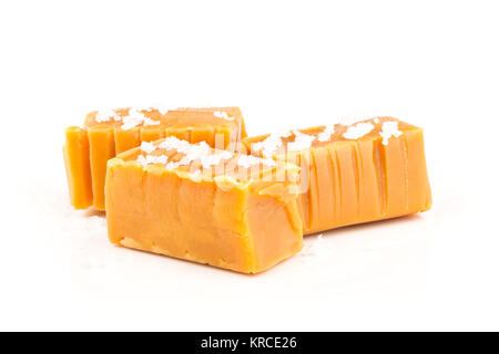 Hand made caramel toffee pieces with sea salt over white background - Stock Photo