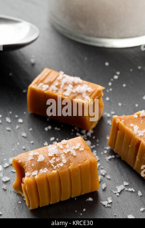 Hand made caramel toffee pieces with sea salt on kitchen stone plate background - Stock Photo
