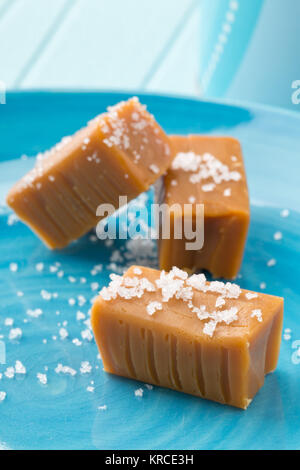 Hand made caramel toffee pieces with sea salt on blue plate on kitchen table - Stock Photo