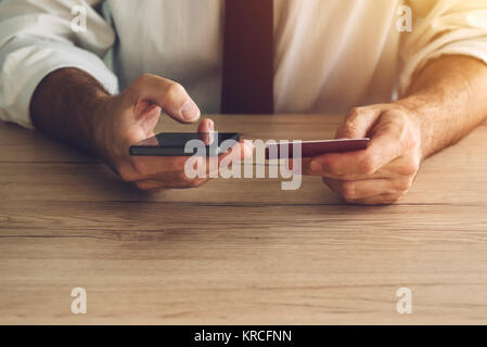 Credit card and mobile payment. Man using smartphone app to make an online bank transaction. Paying and buying on - Stock Photo