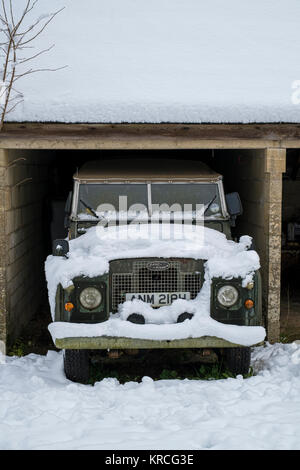 Vintage 1969 Land Rover covered in snow parked in an open garage. Chedworth, Cotswolds, Gloucestershire, England - Stock Photo
