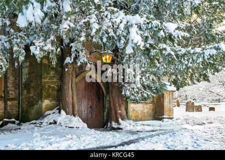 St Edwards church north door yew trees at christmas time in the snow. Stow on the Wold, Cotswolds, Gloucestershire, - Stock Photo