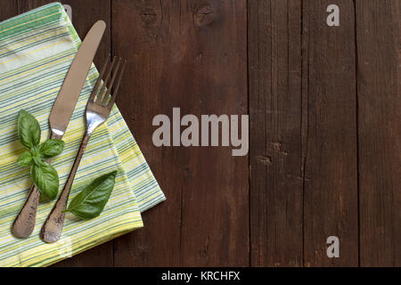 Fork, knife, basil and napkin on a wooden table - Stock Photo