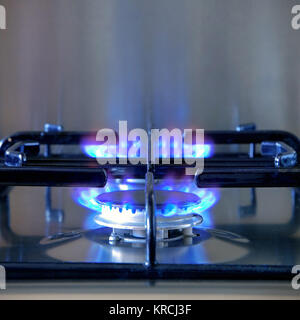Two gas rings alight on a modern brushed steel hob. - Stock Photo