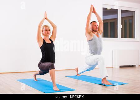 Adult man and woman practicing yoga, Virabhadrasana / Warrior 1 pose - Stock Photo