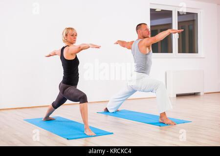 Adult man and woman practicing yoga, Virabhadrasana / Warrior 2 pose - Stock Photo