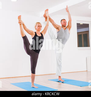 Adult man and woman practicing yoga, Padangusthasana / Extended Hand To Big Toe Pose - Stock Photo
