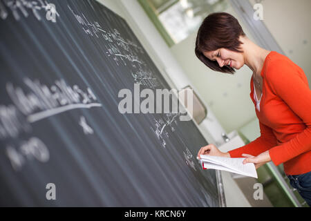 Pretty, young college student writing on the chalkboard/blackboard during a math class (color toned image) - Stock Photo