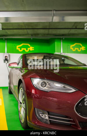 Electric car at a charging point in an underground parking (shallow DOF  color toned image) - Stock Photo