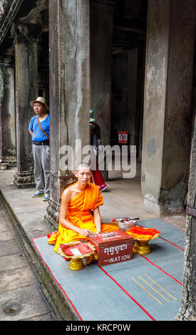 Young Buddhist monk in saffron robes sits in Angkor Wat, a temple complex near Siem Reap in Cambodia, the largest - Stock Photo
