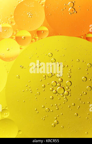 Yellow and orange oil droplet on water - Stock Photo
