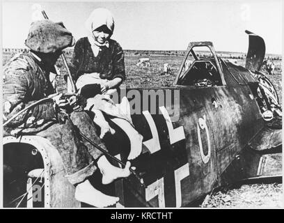 Soviet peasants inspect a shot-down Messerschmitt ME 109 BF. Date: circa early 1940s - Stock Photo